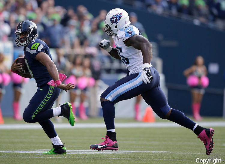 Seattle Seahawks quarterback Russell wilson, left, runs for a first down while being chased by Tennessee Titans defensive end Kamerion Wimbley in the third quarter at CenturyLink Field in Seattle, Washington on  October13, 2013.  Wilson completed 23 passes for 257 yards and rushed 61 yards in the Seahawks 20-13 win over the Titians.    ©2013. Jim Bryant Photo. All Rights Reserved.