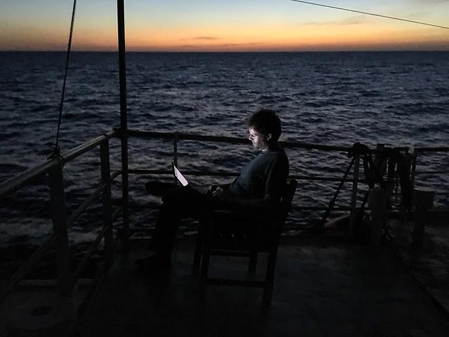 Sea Watch-2.<br /> Die Sea Watch-2 ist zu ihrer 13. SAR-Mission vor der libyschen Kueste.<br /> Im Bild: Ein Crewmitglied sitzt bei Sonnenuntergang auf dem Brueckendeck am Laptop.<br /> 19.10.2016, Mediterranean Sea<br /> Copyright: Christian-Ditsch.de<br /> [Inhaltsveraendernde Manipulation des Fotos nur nach ausdruecklicher Genehmigung des Fotografen. Vereinbarungen ueber Abtretung von Persoenlichkeitsrechten/Model Release der abgebildeten Person/Personen liegen nicht vor. NO MODEL RELEASE! Nur fuer Redaktionelle Zwecke. Don't publish without copyright Christian-Ditsch.de, Veroeffentlichung nur mit Fotografennennung, sowie gegen Honorar, MwSt. und Beleg. Konto: I N G - D i B a, IBAN DE58500105175400192269, BIC INGDDEFFXXX, Kontakt: post@christian-ditsch.de<br /> Bei der Bearbeitung der Dateiinformationen darf die Urheberkennzeichnung in den EXIF- und  IPTC-Daten nicht entfernt werden, diese sind in digitalen Medien nach &sect;95c UrhG rechtlich geschuetzt. Der Urhebervermerk wird gemaess &sect;13 UrhG verlangt.]