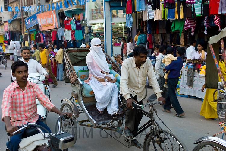 Street scene in holy city of Varanasi, young muslim woman in white burkha rides in rickshaw, Benares, Northern India