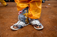 A man whose work it is to clean an ambulance used to carry ebola patients wears a Personal Protection Equipment (PPE) suit, but unfortunately the ambulance service does not have the resources to equip the cleaning staff with rubber boots and thus his toes are left exposed.