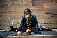 An Aghori Sadhu (holy man) with his human skull at a ghat in Varanasi, Uttar Pradesh, India.