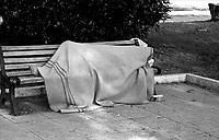 Roma,<br /> Un uomo senza fissa dimora dorme su una panchina in un giardino.