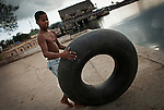 A boy going for a swim with a rubber tyre in Santiago de Cuba.