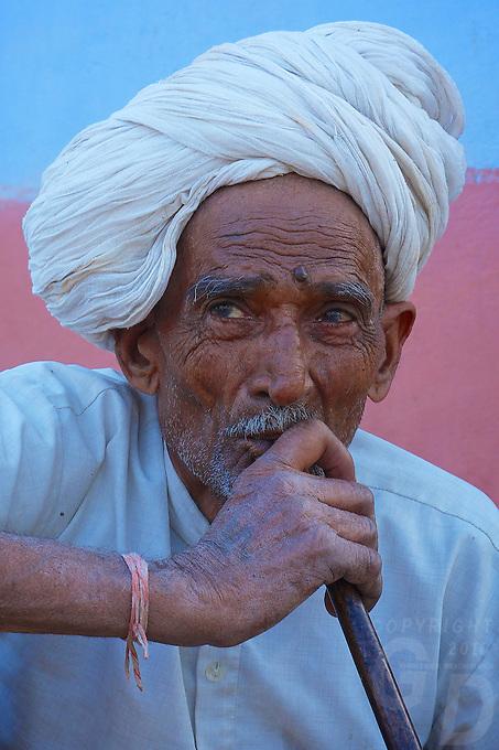 Tribal- Village Elder smoking  on a water pipe Traditional village life in Narhet, Rajasthan, India