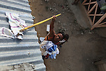 A resident of La Cerca collects dried laundry from a tin rooftop. Barrick and Goldcorp's Pueblo Viejo open-pit gold mine threatens the cocoa-bean producing community of La Cerca. Cotu&iacute;, S&aacute;nchez Ram&iacute;rez, Dominican Republic. April 2012.