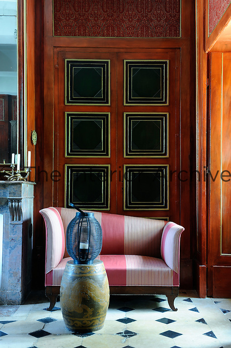 In front of a sofa placed in an alcove of the living room a Chinese urn is used as a table