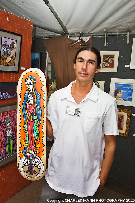 The Santa Fe Spanish Market, held in late July, fills the Santa Fe Plaza with artists, patrons and visitors all celebrating the richness of the Spanish Colonial art tradition side by side with the Contemporary Spanish Art Market.  Contemporary Spanish Market artist Robb Rael desplays one of  his eclectic snow board designs.