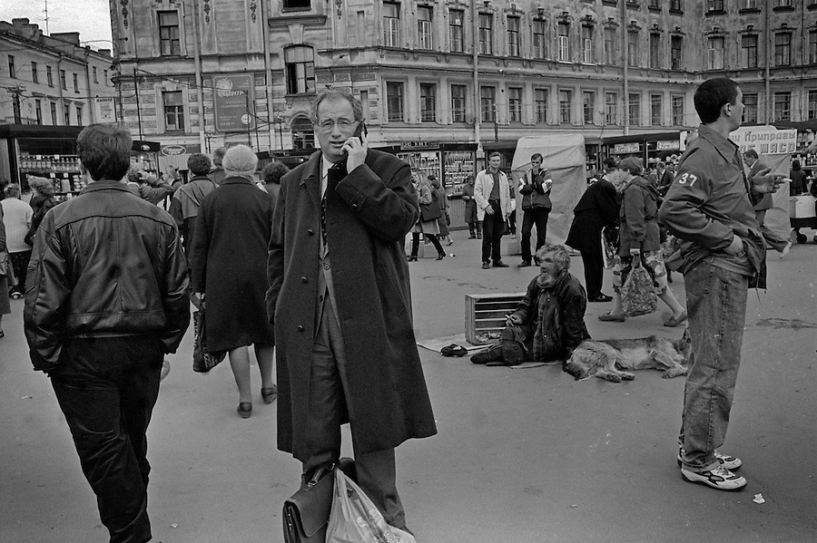 St Petersburg, Russia, September1998..A foreign businessman takes a call on his mobile phone amongst the hustlers and street maketeers of Sennaya Square.