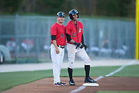 Kannapolis Intimidators manager Justin Jirschele (9) shares a smile with Joel Booker (23) as he stands on third base during the game against the Lakewood BlueClaws at Kannapolis Intimidators Stadium on April 8, 2017 in Kannapolis, North Carolina.  The BlueClaws defeated the Intimidators 8-4 in 10 innings.  (Brian Westerholt/Four Seam Images)