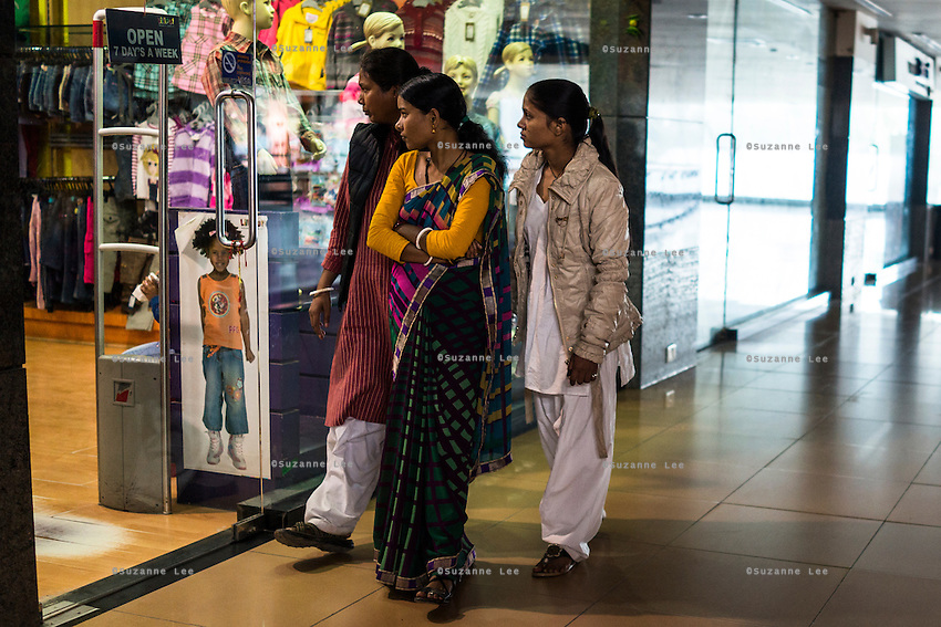 Brinda (center) and Saroj, rescued girls, walk past stores in a mall with  Santwana Manju of Guria while out for a day of shopping fun as a method of therapy, in Varanasi, Uttar Pradesh, India on 24 November 2013. Manju takes the girls under the witness protection program out shopping once in a few months to ease their minds and help them prepare for the court appearances.