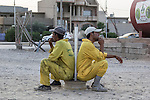 10/10/2014 -- Kirkuk, Iraq -- Two Bangladeshi workers are waiting to go work cleaning the streets in the early morning.
