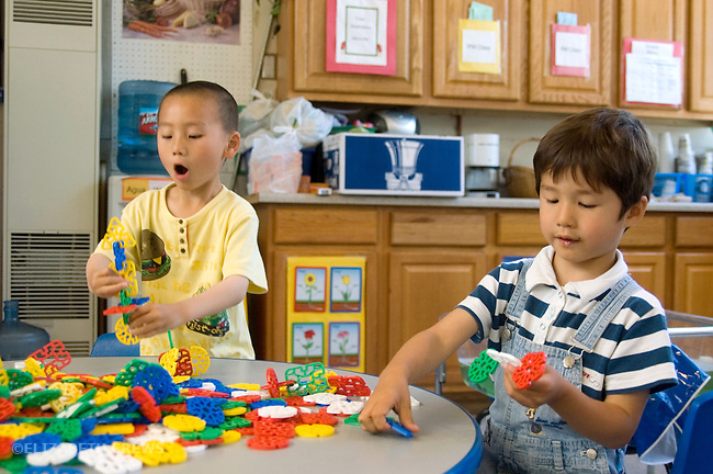 """Berkeley CA Four-year-olds interacting while doing """"parallel play"""" at construction table at bilingual Spanish-English preschool"""