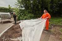 Shawn O'Hanlon uncovers the finished and filtered compost as Officer Richard Orange walks by.