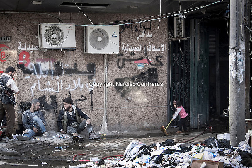 Rashed, a two and a half years-old girl, plays with a broom as she imagens herself helping with the cleaning of the emergency exit at the Dar Al-Shifa hospital while rebel fighters covered by gunpowder sit on the sidewalk as they take a rest after having dropped a wounded comrade rescued from a mortar shelling at the battlefield of Aleppo, Syria.