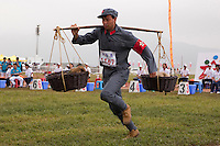 A competitor dressed in a PLA (People's Liberation Army) revolutionary era outfit runs in the shoulder pole race at the Red Games. Held in Junan County, this sporting event is a nostalgic tribute to the communist era.