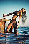 Caucasian female model with long wet hair wearing black swimwear standing outdoors in water in summer