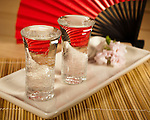 Two glasses of Saki, one filled to overflowing in the tradition of a generous pour