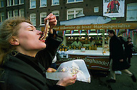 January 1991, Amsterdam, Netherlands --- A woman eats Dutch herring in Amsterdam, Netherlands --- Image by &copy; Owen Franken/CORBIS