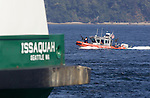 A United State Coast Guard Patrol boat perform escort service for the Washington State Ferry Issaquah near Seattle on August 20, 2009.  The personnel and boats, from the 13th Coast Guard District, provide protection from possible terrorists attacks in support of the Homeland Security for ferries operating from Seattle area ferry terminals to those on the Kitsap Peninsula, Vashion Island, and Bainbridge Island.    © 2009. All Rights Reserved. Jim Bryant