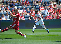 New York midfielder Dane Richards (19) shoots in front of Chicago defender Gonzalo Segares (13).  The Chicago Fire tied the New York Red Bulls 1-1 at Toyota Park in Bridgeview, IL on June 26, 2011.