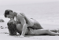 Young couple kissing at beach (B&amp;W)