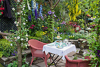 Eating outdoors with wicker chairs, tea set, lush garden, stone patio, coffee cups, luncheon outside on the stone patio with hanging clematis vines, delphinium flowers, achillea, rattan chairs for a colorful private setting
