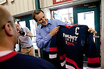 Republican presidential hopeful Tim Pawlenty holds a campaign jersey before playing in a scrimmage hockey game during a campaign stop on Friday, July 22, 2011 in Urbandale, IA.