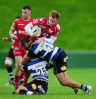 Rhys Patchell of the Scarlets is tackled. Pre-season friendly match, between the Scarlets and Bath Rugby on August 20, 2016 at Eirias Park in Colwyn Bay, Wales. Photo by: Patrick Khachfe / Onside Images
