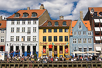 Crowds of people at lunch along Nyhavn or New Harbor canal in Copenhagen, Denmark.