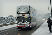 A snow covered bus travels across the bridge after an  early winter snow fall.