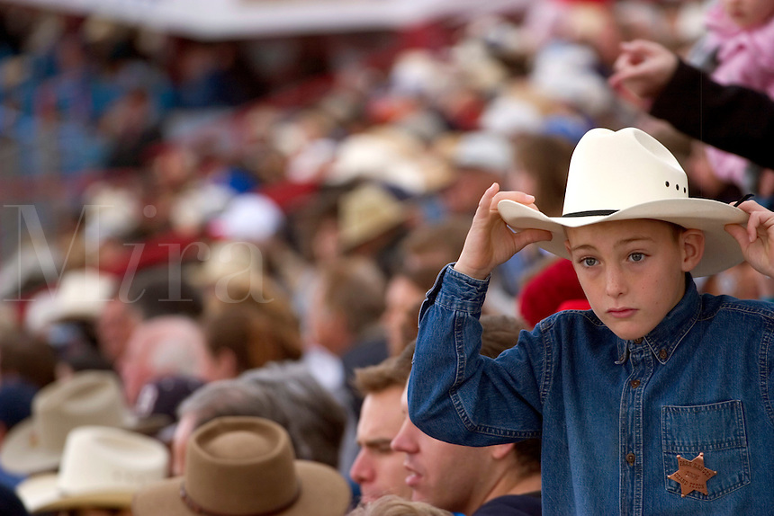 February, 2004 At the Tucson Rodeo, a kid adjusts his hat while watching the competition in Tucson, Arizona.