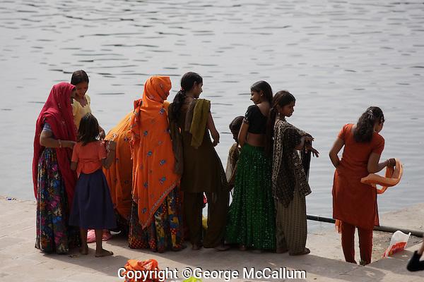 Women at lakeside wearing brightly coloured Sari`s during Pushkar Kartik Poornima festival. Ajmer district, Rajasthan, India