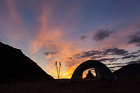 Camper watches a brilliant sunrise from the tent on a mountain ridge in the Arrigetch Peaks, Gates of the Arctic National Park, Alaska.
