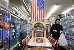 A customer walks past a Wurlitzer juke box on sale for ¥1.6 million (U.S.$19,709) at Shimura Seisakusho, a shop specializing in retro American diner goods, in the Kappabashi district of Tokyo, Japan on Nov. 10 2010. Often called Tokyo's Kitchen Town, stores in Kappabashi still mainly caters to professionals in the catering industry, though is becoming increasingly popular with foreigners hunting for unique souvenirs..Photographer: Robert Gilhooly