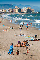 Valencia, Spain, September 2013. People at the beach on the seaside of Valencia.  In the middle of the Spanish Mediterranean coastline lies Valencia, a beautiful city backed by mountains and plains. The city itself is boasts beautiful architecture from the historic to avant-garde. Valencia is also famed for its art galleries and fabulous local cuisine, such as juicy Valencia oranges and traditional Spanish paella, which originated from here. A good way to explore the city is by bicycle. Photo by Frits Meyst