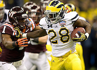 Fitzgerald Toussaint of Michigan runs the ball away from Virginia Tech defenders during Sugar Bowl game at Mercedes-Benz SuperDome in New Orleans, Louisiana on January 3rd, 2012.  Michigan defeated Virginia Tech, 23-20 in first overtime.