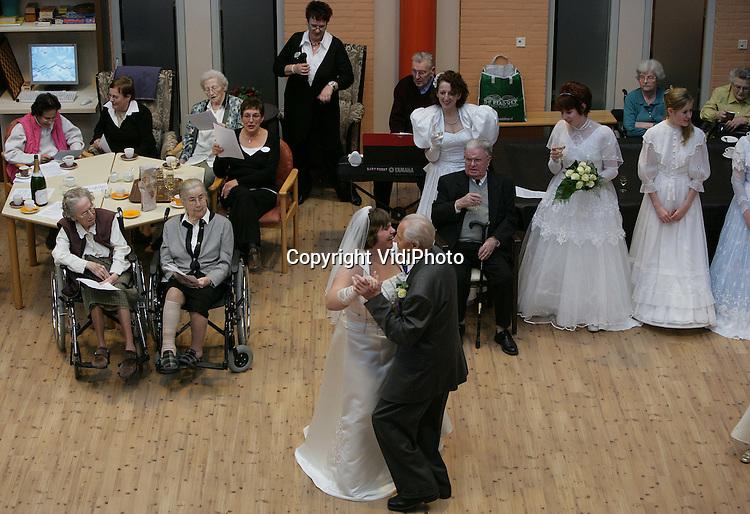 Foto: VidiPhoto..HERVELD - Een ongebruikelijke gebeurtenis in zorgcentrum De Hoge Hof in Herveld zaterdag. Daar werd door bewoners en verplegend personeel een bruidsshow gehouden. Mooiste koppel werd bewoner Walter Timmer (81) met zijn gelegenheidspartner, de 28-jarige Mariëlle Willems. Hoewel dhr. Timmer deze week 60-jaar getrouwd was, droeg hij voor het eerst een trouwpak. Zestig jaar geleden had hij geen geld om er een te kopen. De show was spontaan bedacht en georganiseerd door de bewoners zelf. Zowel deelnemers als publiek raakten soms geëmotioneerd. Foto: Het winnende koppel opent het feest met een dans.
