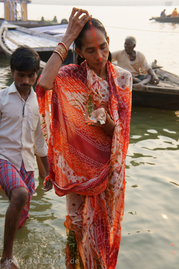 after bath in holy river Ganges, a wife paints special tika on her forehead, showing her married status during chat mata, holy days, where especially woman  pray for relief -  in holy city Varanasi, India 31. Oktober 2011 (chat mata is also called Dala chhath). In this ceremony women gather at the river and pray for sons and good luck of her family (a woman without a son is belived to end up in hell, also a widow is believed to be cursed and can be expelled by the family).God of the sun, Surya is asked for help in Dala chhath. Surya is one of the most acient gods in India, already known in Vedic times, where Shiva and Brahma were still unknown.
