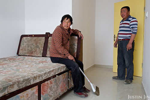 Chen Hua, 50, moves into her new urban home in Liaocheng city in the northeastern Chinese province of Shangdong.<br /> <br /> Her former village house was bulldozed by the government three years ago to make way for high-rise development. <br /> <br /> In the four years between her rural home being razed and the completion of her new city apartment, she and her family lived in temporary village housing such as this one. <br /> <br /> China is pushing ahead with a dramatic, history-making plan to move 100 million rural residents into towns and cities between 2014 and 2020 &mdash; but without a clear idea of how to pay for the gargantuan undertaking or whether the farmers involved want to move.<br /> <br /> Moving farmers to urban areas is touted as a way of changing China&rsquo;s economic structure, with growth based on domestic demand for products instead of exporting them. In theory, new urbanites mean vast new opportunities for construction firms, public transportation, utilities and appliance makers, and a break from the cycle of farmers consuming only what they produce.<br /> <br /> Urbanization has already proven to be one of the most wrenching changes in China&rsquo;s 35 years of economic reforms. Land disputes rising from urbanization account for tens of thousands of protests each year.