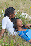 Twin sisters relaxing on a prairie hill after school.