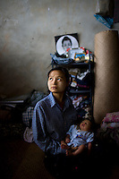 22 year old Thanda with her newborn baby that was born with no medical assistance during Cyclone Nargis, which hit the Irrawaddy Delta on 02/05/2008. She now shelters alongside other refugees from the 7th ward, Hlaingthaya township in Rangoon (Yangon), in the Shwe Than Lwin shopping complex, which is under construction and has acted as a small refugee centre. Her new born baby is popularly known as Nargis baby, though her real name is Nan Watyi...
