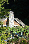 The water and view-facing outside of this wood-shingled, waterfront weekend vacation retreat on Washington State's Vashon Island boasts the large rock chimney, an arbor bearing a massive grape vine that partially shades the brick patio, and curving beds sporting perennials, shrubs, and grasses carved into the lawn.