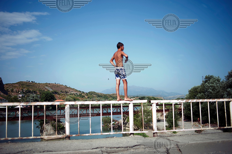 A boy stands on the edge of a bridge preparing to jump in the river.