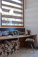 A simple home office has been created using a recycled plank of wood placed beneath a picture window
