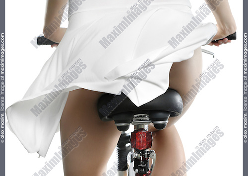 Sexy young woman in white fluttering summer dress riding a bicycle Isolated silhouette on white background