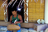 Man preparing betelnut (used for ritual daily chewing) at his house, Yap Micronesia