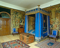 Tapestries line the walls of this bedroom which features a four-poster bed and chairs clad in bright blue damask