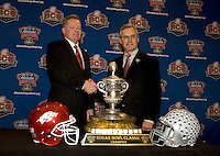Ohio State head coach Jim Tressel and Arkansas Head Coach Bobby Petrino shake hands with the Sugar Bowl Championship trophy for photo opportunity during the Head Coaches' Press Conference at Marriott at the Convention Center in New Orleans, Louisiana on January 3rd, 2011.