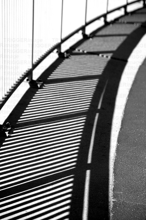 The metal railing of a bridge railing casts a shadow.