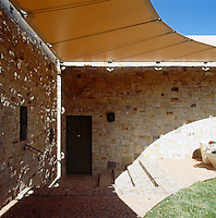 In the inner courtyard of a contemporary adobe house in New Mexico shade is achieved by a circular canvas awning